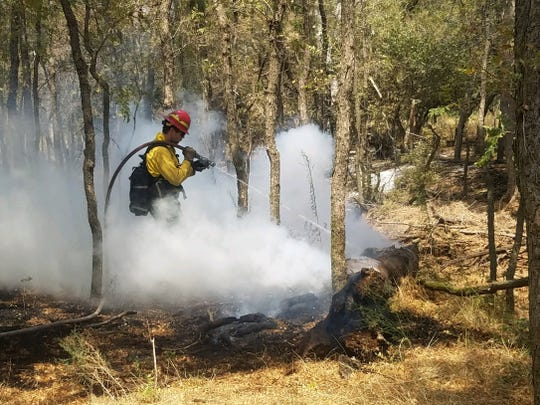 A firefighter works to extinguish a hot spot inside the Copper Breaks Fire.