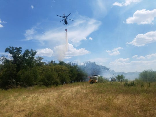 A helicopter drops water on a section of the Copper Breaks Fire to support an engine working the area as well.