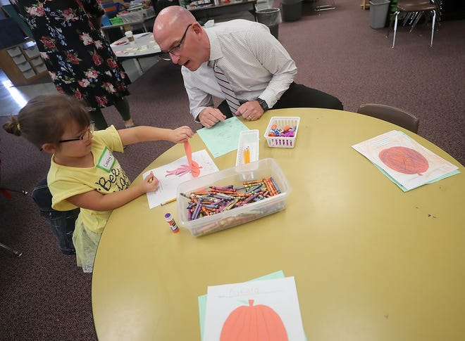 Casey Wood, 5, shows South Kitsap School District Superintendent Tim Winter the project she is working on at East Port Orchard Elementary School on Thursday. Winter is beginning his tenure as SKSD's superintendent.