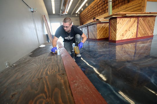 Cody Morgan oils a wooden platform along the wall at Peninsula Beverage Collective in Port Orchard on Thursday.