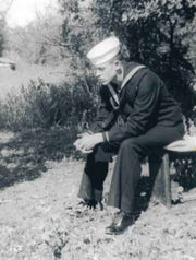 Calvin Palmer, the older of the two brothers, prays in his Navy uniform.