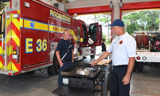 Battlaion Chief Ed Syfrett, right, prepares dinner at Rockledge Fire Station No.36, where members of several stations were invited to enjoy a meal that included shrimp and grits.