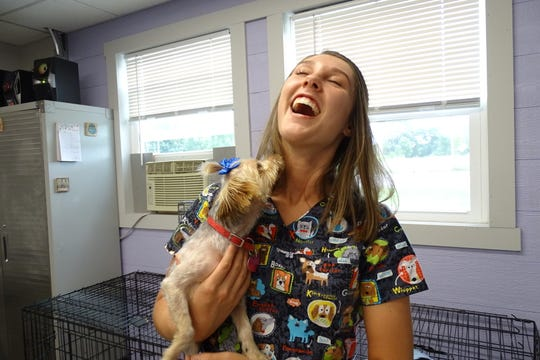 Sarah Campbell, the 19-year-old owner of Galion Shampooch, gets a kiss from Everly, one of her clients.