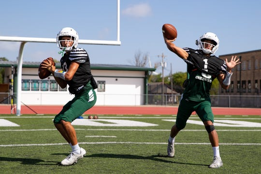 Taft quarterbacks throw as players run drills during practice on Monday, Aug. 19, 2019