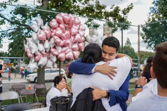 Academy of Americas principal Nicholas Brown hugs Diana Hernandez of Detroit at St. Hedwig Park in southwest Detroit on Thursday, Aug. 22, 2019 during a vigil for her niece 9-year-old Emma Hernandez of Detroit, who was killed Monday afternoon by three dogs while riding her bike in an alley on the west side of Detroit near her home. Hernandez attended the school in southwest Detroit.