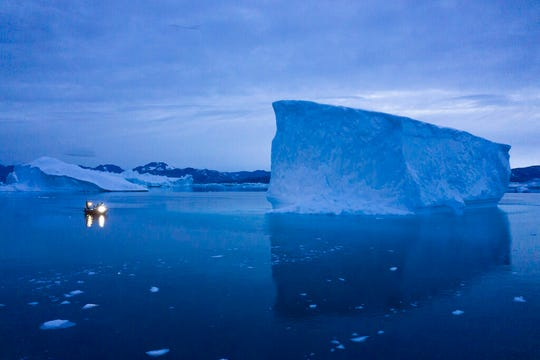 FILE - In this Aug. 15, 2019, file photo, a boat navigates at night next to large icebergs in eastern Greenland. As warmer temperatures cause the ice to retreat the Arctic region is taking on new geopolitical and economic importance, and not just the United States hopes to stake a claim, with Russia, China and others all wanting in.