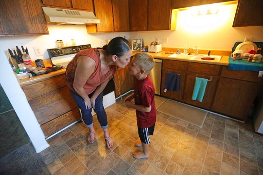 Misty Dotson kisses her son at their home Tuesday, Aug. 20, 2019, in Murray, Utah. Dotson is a 33-year-old single mother of two boys, ages 12 and 6, who goes to Planned Parenthood for care through the Title X program. Dotson is among the 39,000 people received treatment from Planned Parenthood of Utah in 2018 under a federal family planning program called Title X. The organization this week announced it is pulling out of the program rather than abide by a new Trump administration rule prohibiting clinics from referring women for abortions.