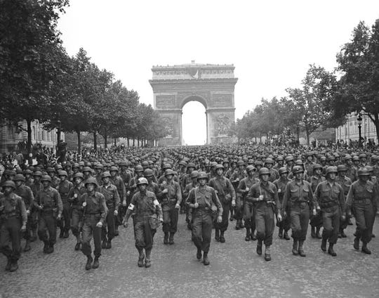 In this Aug. 29, 1944 file photo, U.S. soldiers of Pennsylvania's 28th Infantry Division march along the Champs Elysees, the Arc de Triomphe in the background, four days after the liberation of Paris, France.