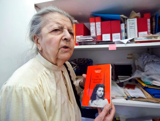 This Tuesday Aug. 19, 2014 photo shows French poet, journalist, and member of the French Resistance Madeleine Riffaud answering a reporter during an interview with the Associated Press in Paris. Riffaud holds a book she wrote, with on the cover, a photo of her at the time of WWII. Riffaud had a code name, Rainer, and a gun she called Oscar. Just weeks before turning 20, she aimed her weapon at a Nazi officer and shot him dead on a Paris bridge.