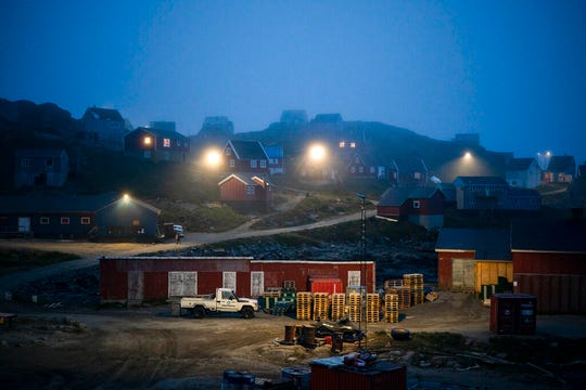 In this Aug. 15, 2019, file photo, early morning fog shrouds homes in Kulusuk, Greenland.