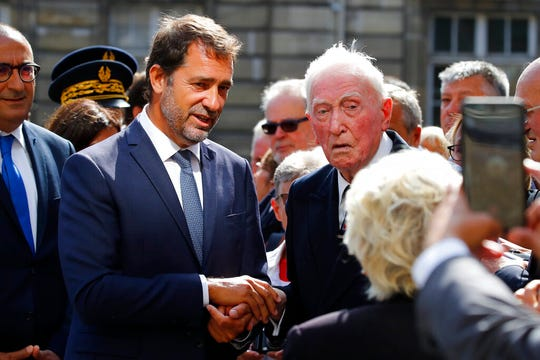 French Interior Minister Christophe Castaner, center left, meets Robert Pincon, a French police officer enrolled in Liberation of Paris fighting on Aug.19, 1944, attends a ceremony marking the 75th anniversary of the Liberation of Paris,Tuesday, Aug. 20, 2019 in Paris.