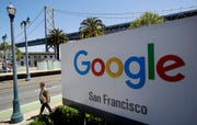 In this May 1, 2019, file photo a man walks past a Google sign outside with a span of the Bay Bridge at rear in San Francisco. Google said it will propose plans, to make surfing the web more private, for debate before the organizations that set common rules for the Internet. That means Google wants the entire web to adopt the new rules, instead of just installing them on its own Chrome browser.
