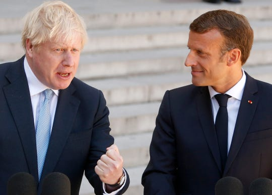 French President Emmanuel Macron, right, and Britain's Prime Minister Boris Johnson talk to the media Thursday, Aug. 22, 2019 in Paris.