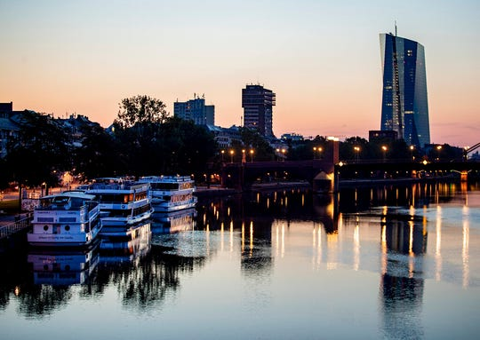 The sun rises next to the European Central Bank at the river Main in Frankfurt, Germany, early Thursday, Aug. 22, 2019.