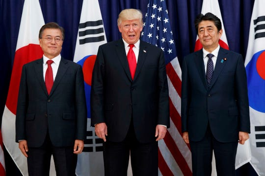 FILE - In this July 6, 2017, file photo, U.S. President Donald Trump, center, meets with Japanese Prime Minister Shinzo Abe, right, and South Korean President Moon Jae-in before the Northeast Asia Security dinner at the U.S. Consulate General Hamburg in Germany. In August 2019, Trump angered some Asian American voters after the New York Post reported that he mocked the accents of Moon and Abe at a fundraiser in the Hamptons.