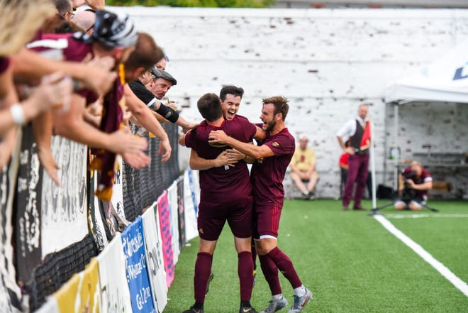 Marcello Borges celebrates with DCFC teammates Seb Harris and James Vaughan after scoring the opening goal in his team's 2-1 victory over Chattanooga FC last Saturday.