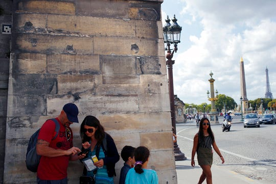 Tourists stand under bullet holes, which remain from the fight for the liberation of Paris, mid August 1944, along the wall of the Tuileries Garden at the place de la Concorde in Paris, Tuesday, Aug. 20, 2019. Paris suffered no major damage during the fighting, though official edifices still bear the bullet holes of fighting.