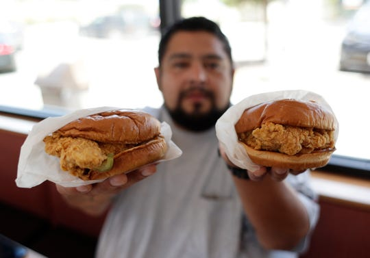 Randy Estrada holds up chicken sandwiches at a Popeyes, Thursday, Aug. 22, 2019, in Kyle, Texas.