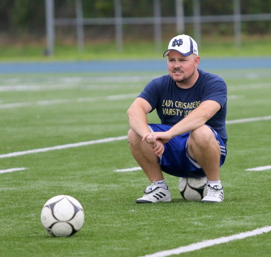 Elmira Notre Dame girls soccer head coach Kevin Weber rests during a water break at  practice Aug. 22, 2019 at Brewer Memorial Stadium. Weber is co-head coach with his dad, Steve Weber.
