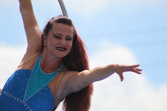 Crina Alvarez uses a hula hoop suspended 15 feet in air to perform contortion moves at the Sandusky County Fair.