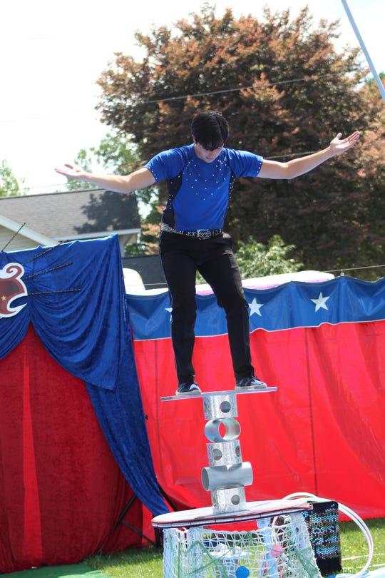 Cirque Mundial performer Gianni Alvarez balances on five cylinders during a performance at the Sandusky County Fair.
