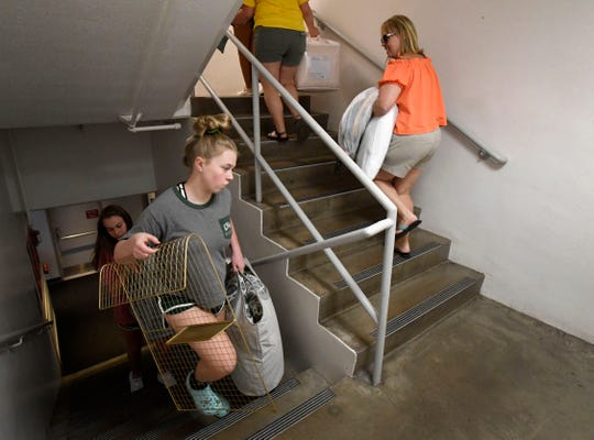 Students carry their belongings up the stairs as they move in to Westfall Hall during Colorado State University's move in on campus in Fort Collins, Colo. on Thursday, August 22, 2019.