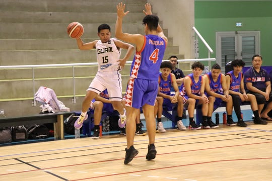 Guam's Isaiah Malig, No. 15,  looks to bounce the ball off an opponent to keep possession during their FIBA U17 Oceania Championship game Aug. 21 in New Caledonia.