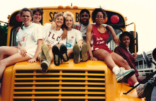 The state qualifiers from Henderson County's 1990 girls track team hop on the bus as they finished as the state runner-up. Team members were, from left, Alison Staples, Lisa Hayden, Ginger Smith, Gretchen Enyart , Leslie Hay, Tracey Folden and Desiree Tramill.