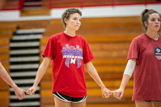 Bridget Balcerak laces her pinkies' with her teammates during practice Aug. 21. at Martinsville High School.