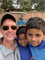 Iowa City's Bobby Jett poses in the city of Bodh Gaya, India, with two young boys he met on the street. As he travels the small towns and back roads of the nation, he reports that most Indians are very willing to allow photographs.