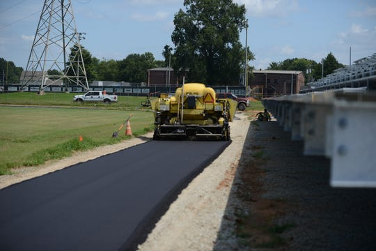 Crews finish up the asphalt track around the field at South Side High School's football stadium on Wednesday.