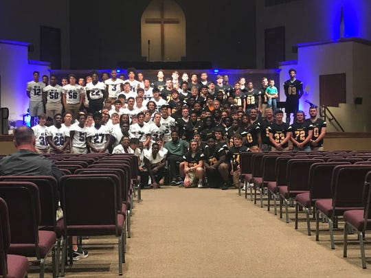 Every varsity football player from Milan and Peabody stop for a picture with motivational speaker Timothy Alexander after he talked with them about appreciating the experience that is high school football on Wednesday at Chapel Hill Baptist Church.