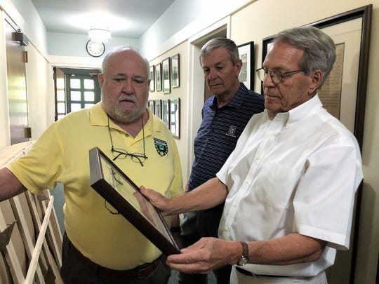 Doug McKamey, Rick Jenkins and Frank Gray look at a photograph of the old St. John's Church building during a tour on August 21, 2019.