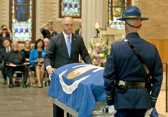 Louisiana Governor John Bel Edwards places a state flag onto the casket during a Celebration of Life Interfaith Service for former Louisiana Gov. Kathleen Babineaux Blanco, at St. Joseph Cathedral in Baton Rouge, La., Thursday, Aug. 22, 2019. Thursday was the first of three days of public events to honor Blanco, the state's first female governor who died after a years long struggle with cancer.
