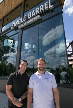 Single Barrel Social owner Chris Klebba, left, and Director of Operations Tyler Herron stand in front of the restaurant, bar and entertainment venue in Brighton, Thursday, Aug. 22, 2019