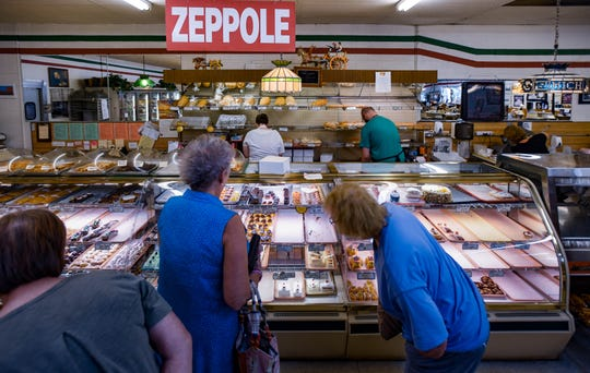 Shoppers peruse a selection of pastries Wednesday, Aug. 21, 2019, at Roma Bakery in Lansing.  After 50 years of serving authentic Italian foods and pastries, Roma Bakery will be closing at the end of September.