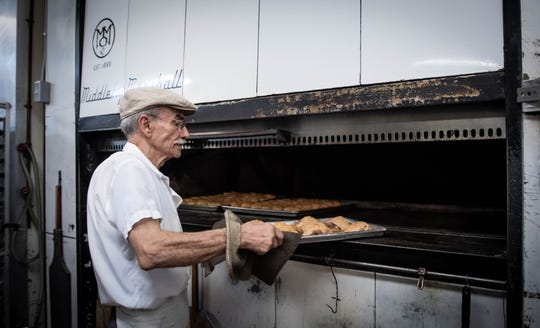 Sostine Castriciano, co-owner of Roma Bakery in Lansing, pulls baked chicken from the oven, Wednesday, Aug. 21, 2019, at Roma Bakery in Lansing.  The baked chicken will be dinner for him and wife, Mena, who will retire at the end of September after 50 years of serving Italian foods and pastries.