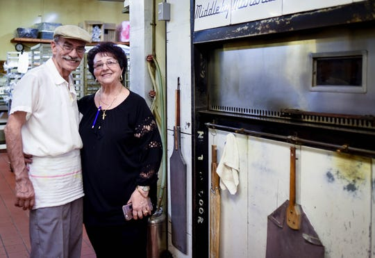 """Sostine and Filomena """"Mena"""" Castriciano pose for a portrait Wednesday, Aug. 21, 2019, at their Roma Bakery in Lansing.  After 50 years of serving authentic Italian foods and pastries, they will be retiring at the end of September."""