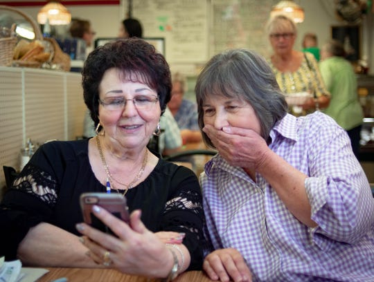 """Mena Castriciano of Roma Bakery, left, shows Sue Watson pictures of her grandchildren, Wednesday, Aug. 21, 2019. Watson has been buying baked goods at Roma since 2007.  """"Lansing will never be quite the same. Roma is a big piece of its history,"""" she said. After 50 years of serving Lansing with their authentic Italian foods and pastries, Mena and husband Sostine will close at the end of September."""