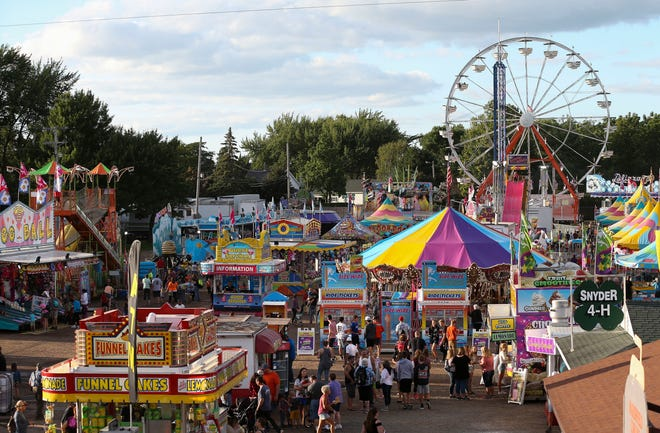 Crowds mill through the midway on Wednesday, August 21, 2019, at the Central Wisconsin State Fair in Marshfield, Wis.