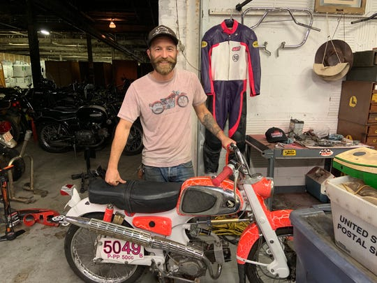 Andy Pickett with the 1963 Honda motorcycle and racing suit at his shop in Milwaukee.