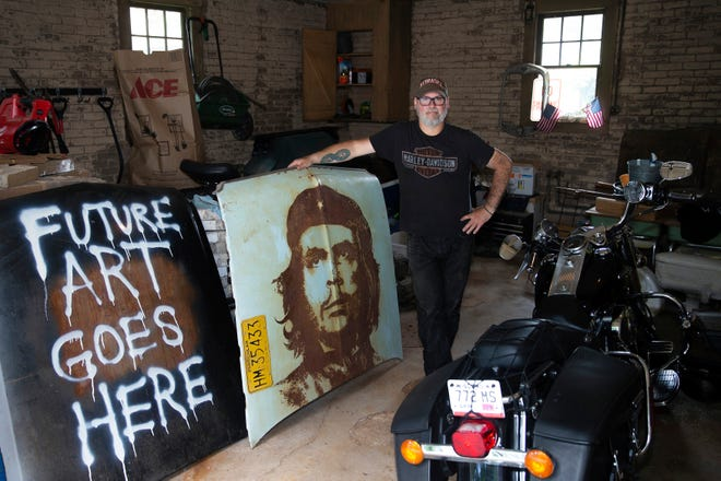 """Michael Stodola poses with his latest handiwork: a portrait of Che Guevara on the hood of a """"Che""""vrolet. Stodola, a brand manager at Lakefront Brewery, has been making car-hood portrait art since 2010. The Guevara portrait was the second one he complete, in 2012."""