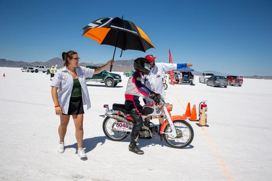 Andy Pickett prepares to make a run at the Bonneville Salt Flats Race Track in Utah. At left is his racing team member Ellie Dennis.