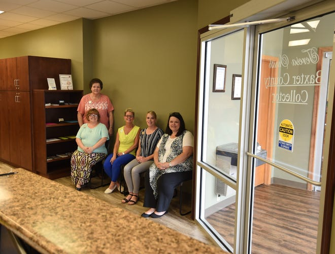Employees with the Baxter County Collector's Office (from left) Karen Risely, Tina Studnar, Teresa Smith, Kim Williams and Yvette Sigafus sit in the new lobby area of their office Thursday afternoon. The office recently completed a 10-month remodeling that added automatic doors and the lobby area to the office.