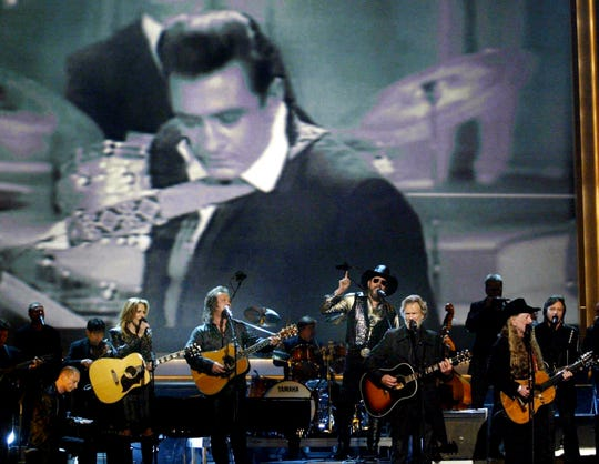 Sheryl Crow, left, Travis Tritt, Hank Williams Jr., Kris Kristofferson and Willie Nelson perform a tribute to Johnny Cash during the 37th CMA Awards show Nov. 5, 2003.