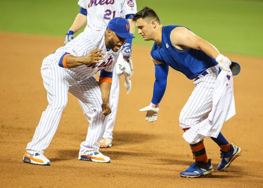 Aug 21, 2019; New York City, NY, USA; New York Mets left fielder J.D. Davis (right) celebrates with second baseman Robinson Cano (24) after hitting a game winning RBI single in the tenth inning to defeat the Cleveland Indians at Citi Field. Mandatory Credit: Wendell Cruz-USA TODAY Sports