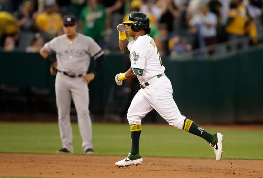 Oakland Athletics' Khris Davis celebrates as he runs the bases after hitting a two-run home run off New York Yankees' J.A. Happ during the second inning of a baseball game Wednesday, Aug. 21, 2019, in Oakland, Calif. (AP Photo/Ben Margot)