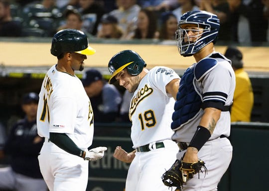 Aug 21, 2019; Oakland, CA, USA; Oakland Athletics shortstop Marcus Semien (10) celebrates with catcher Josh Phegley (19) behind New York Yankees catcher Gary Sanchez (24) after scoring Phegley on a two run home run during the third inning at Oakland Coliseum. Mandatory Credit: Kelley L Cox-USA TODAY Sports