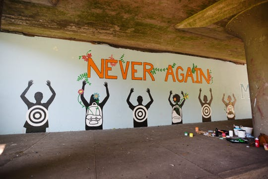 Photo of the gun violence mural being painted by former Montclair High School students under the NJ Transit overpass near Essex Avenue in Montclair on 08/22/19.