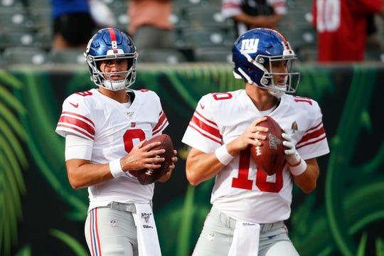 New York Giants quarterback Daniel Jones, left, practices alongside quarterback Eli Manning (10) before an NFL preseason football game, Thursday, Aug. 22, 2019, in Cincinnati.